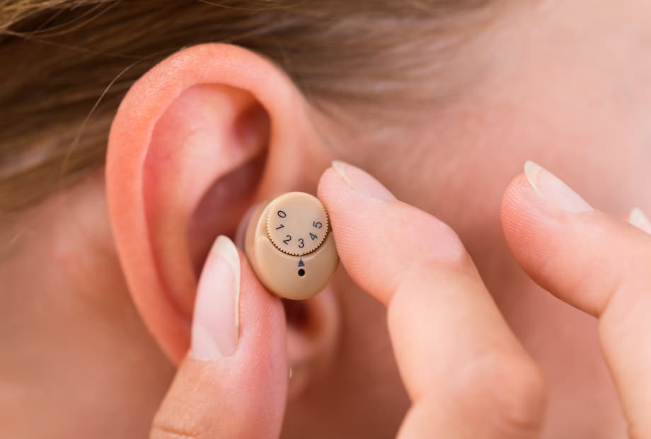Hearing aid being placed on ear