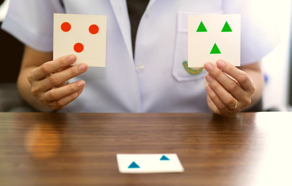 Therapist holding cards with different shapes to help patient recover cognitive skills